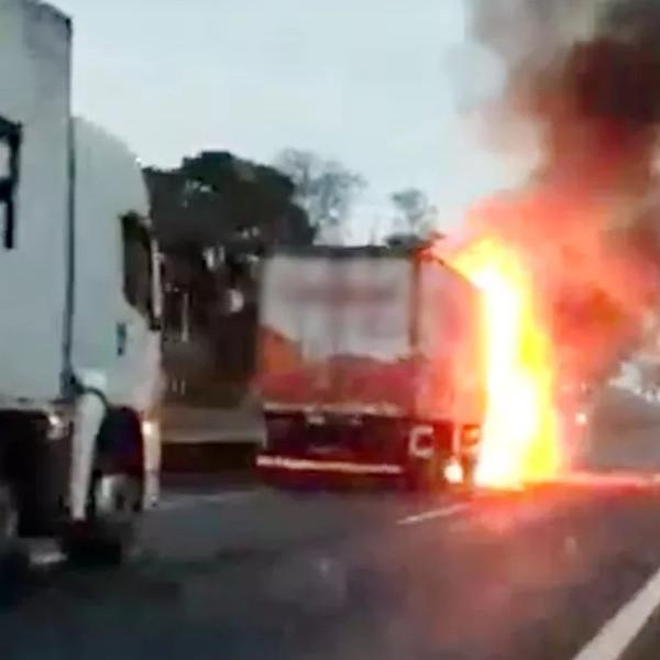 Carro prensado por caminhões pega fogo em rodovia e motoristas escapam ilesos